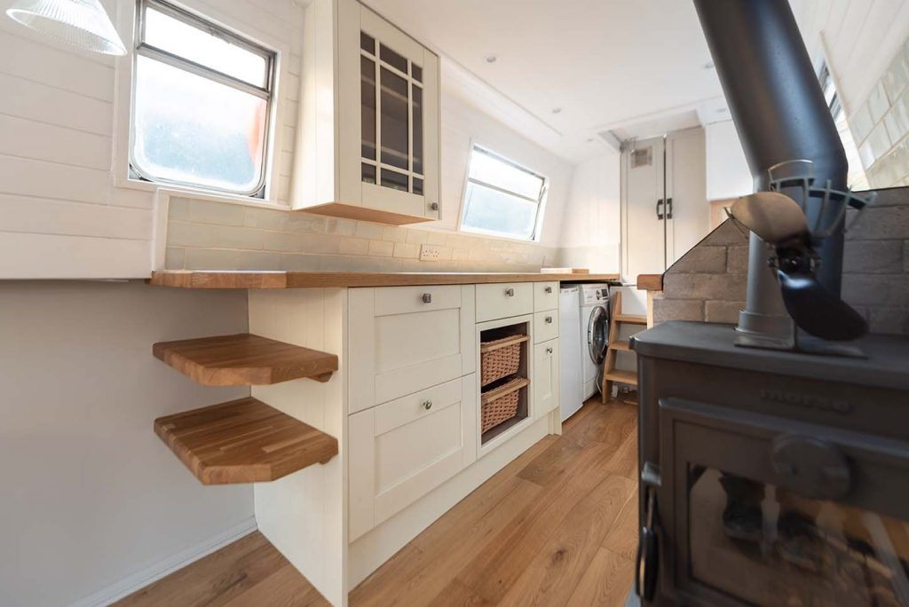 Narrowboat galley style kitchen.  White shaker cabinets with oak butchers block worktop and shelves. Glass fronted cabinet on wall above. Multi fuel stove in the fore-ground