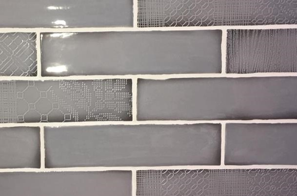 grey brick pattern tiles with embossed patterns. white grout between