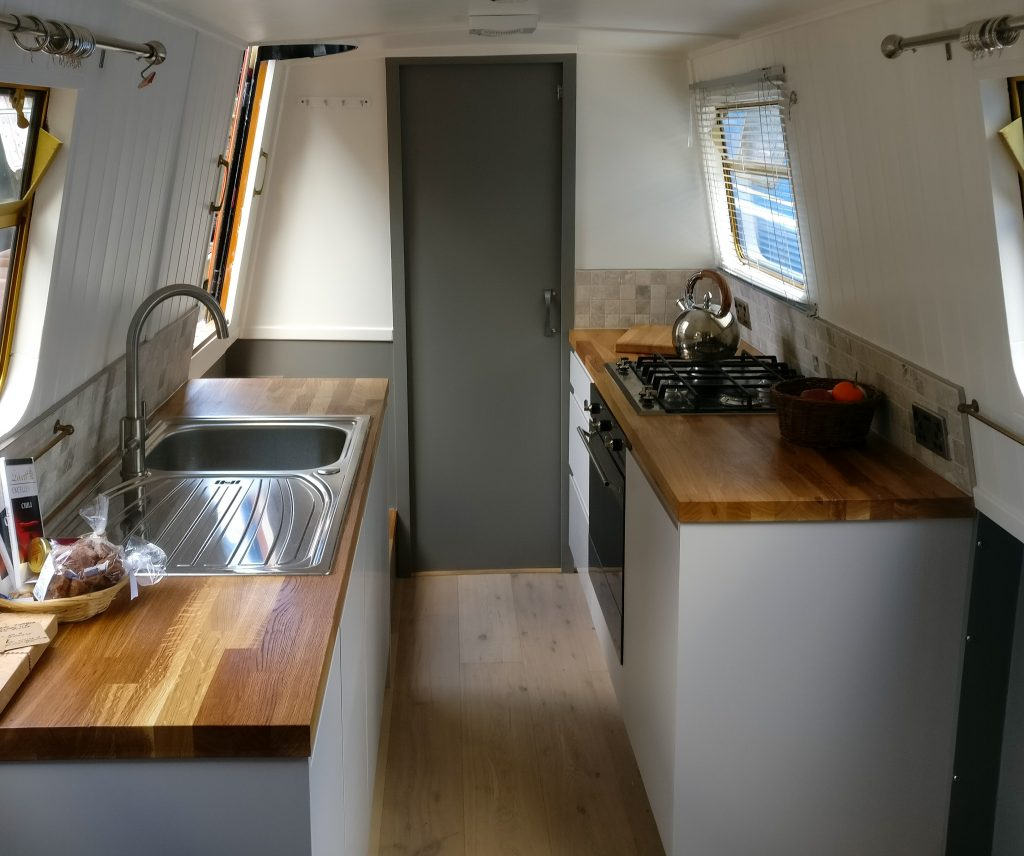 Light grey galley style kitchen with oak butchers block worktop and stainless steel sink in a narrowboat