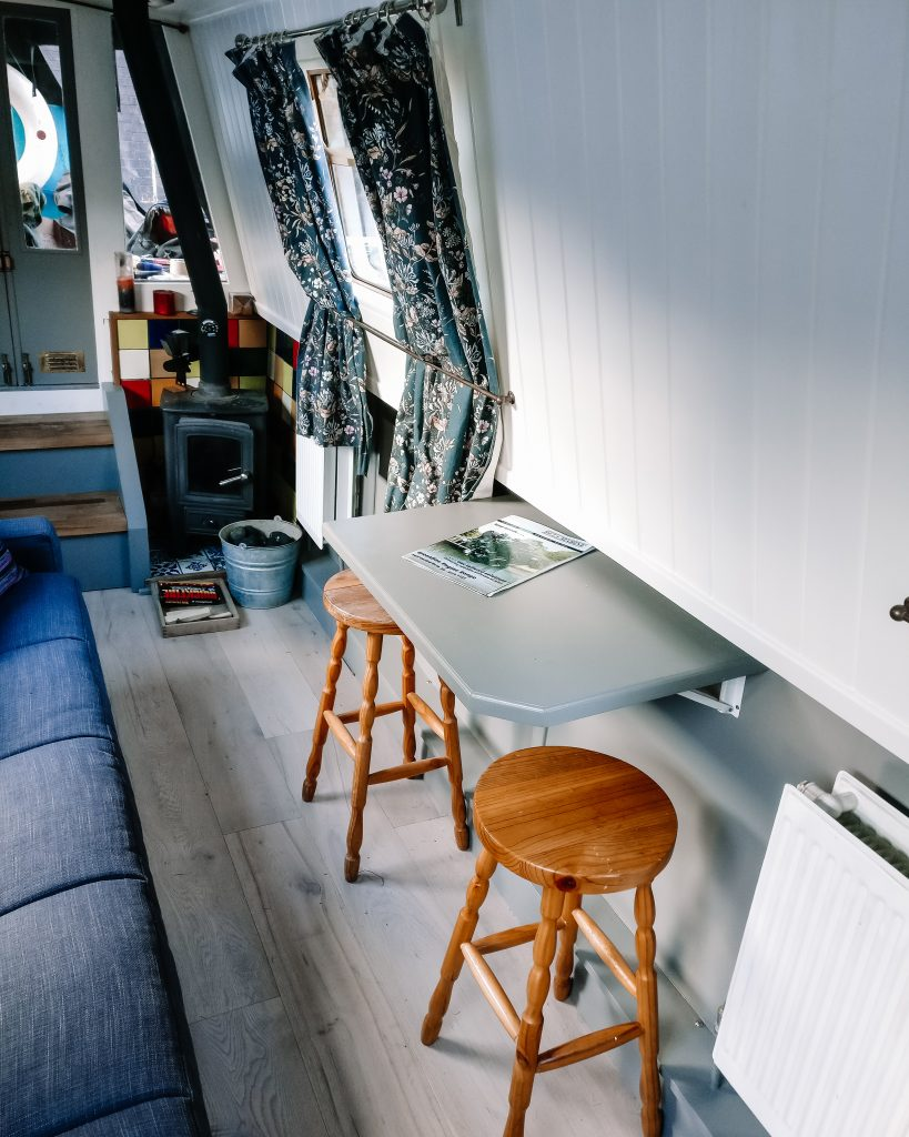 Narrowboat salon, showing fold up table wth stools and sofa.  Light grey beneath the gunwale and qhit above. Multi fuel stove in the corner next to storage steps