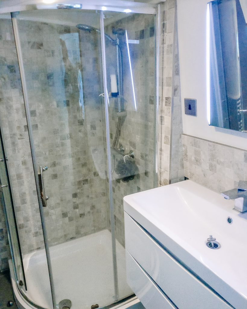 Quadrant shower on a narrowboat with travertine mosiac tiles and shortened glass (1700) glass enclosure
