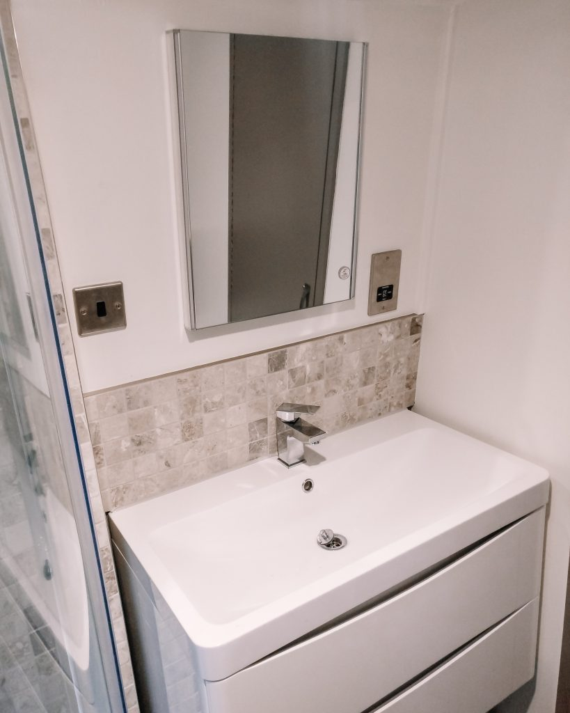 White wall hung vanity unit with LED mirror and travertine splashback
