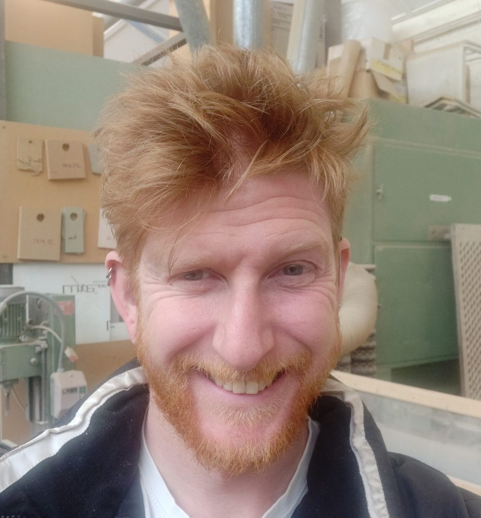 Daniel Cluett Red hair and beard smiling man in his thirties stood in front of workshop equipment